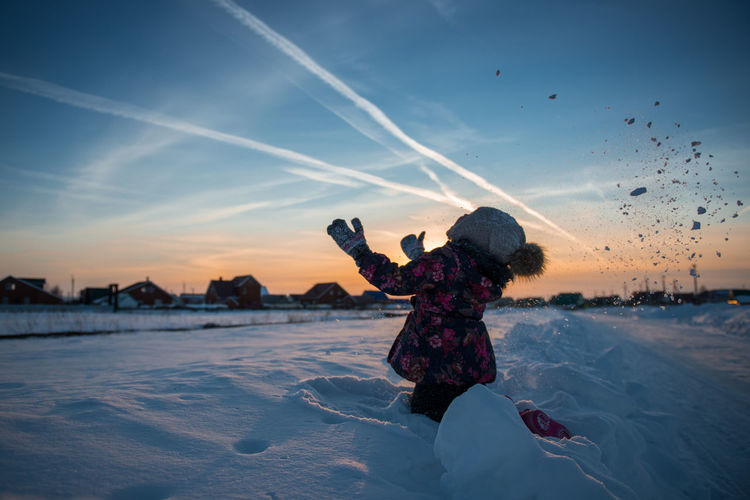 Full length of woman on snow covered land against sky during sunset