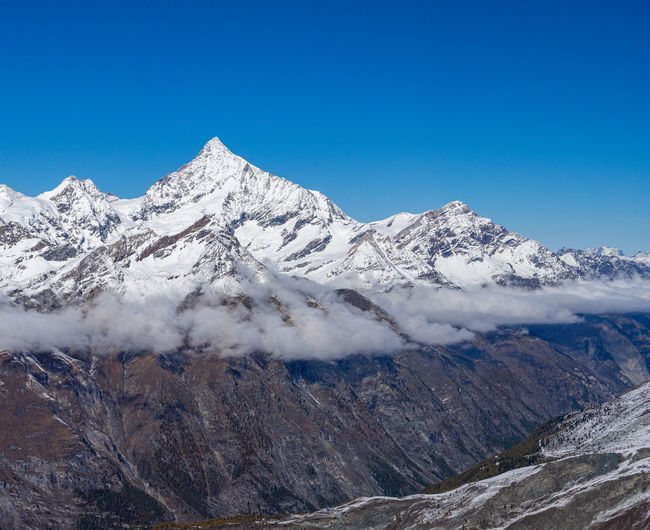 Scenic view of tje weisshorn and surrounding snowcapped mountains against clear blue sky