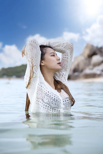 Woman with reflection in water against sky
