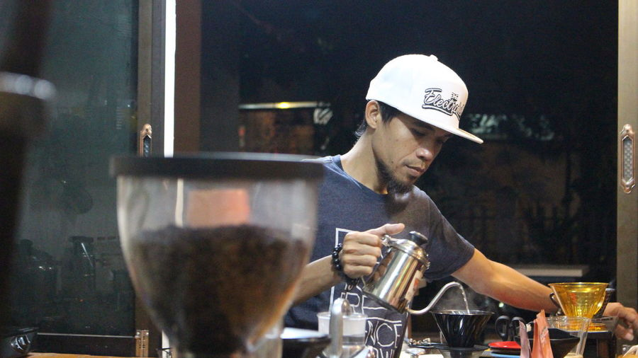 Full length of man pouring coffee in cafe