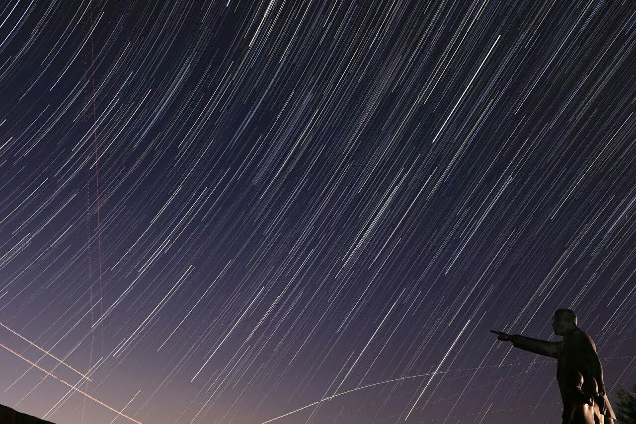 Low Angle View Of Male Statue Against Star Trails In Sky At Night