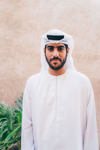 Portrait of young arabic man standing against beige wall
