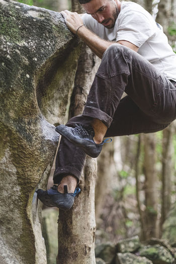 Midsection of man sitting on rock in forest