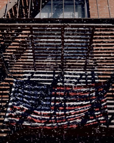 American flag. Americana American EyeEm Best Edits EyeEm Best Shots EyeEm Gallery EyeEm Selects EyeEm ShotOnIphone Building Light And Shadow Fire Escape Snow Flag American Flag Building Exterior