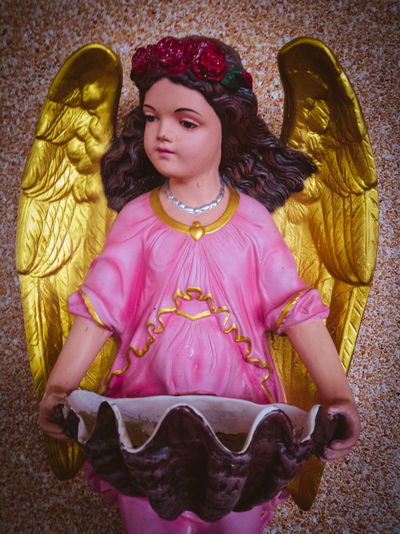 Status of little angel holding a shell. Indoors  Beautiful Status Angels Gold Wings Holding Religion Christ