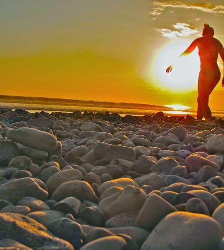 Silhouette woman walking on beach against orange sky