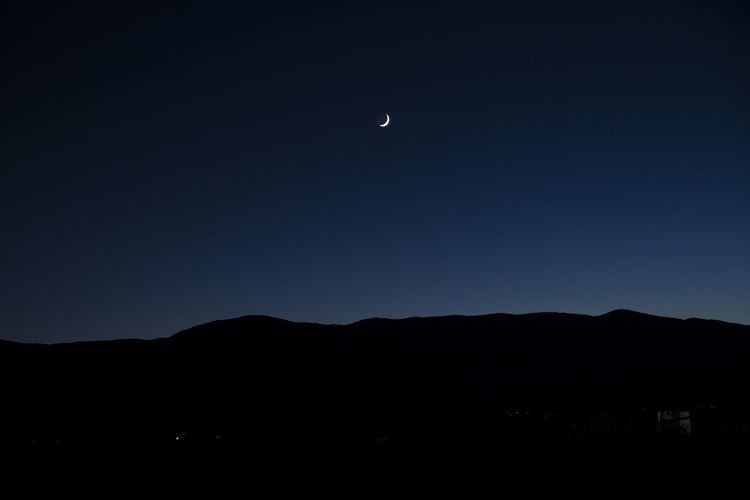 Silhouette mountains against clear sky at night