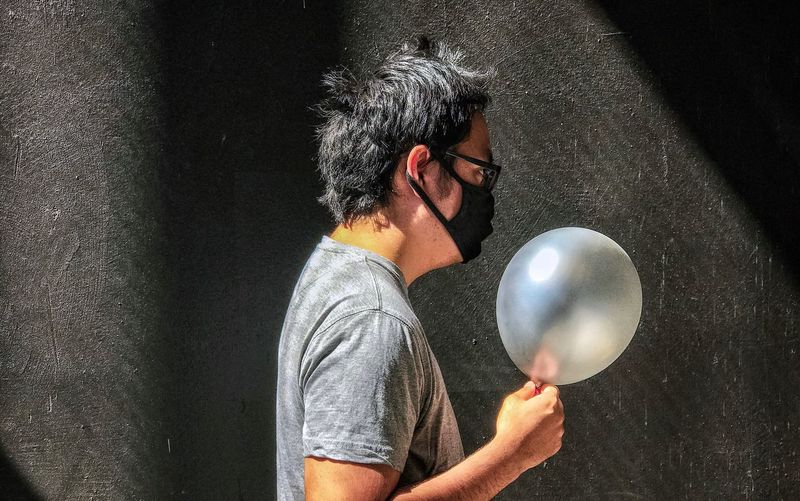 Portrait of young man holding balloons