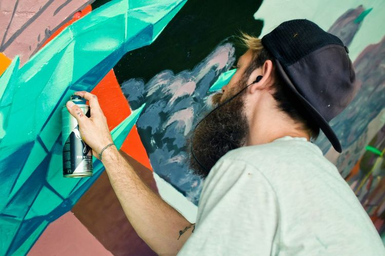 Street Artist Painting Graffiti With Aerosol Can On Wall