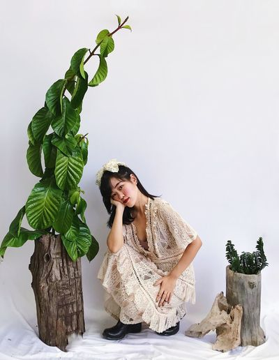 Young woman looking away while sitting on plant against wall