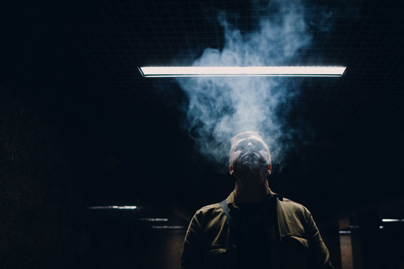 Man smoking while standing against black background
