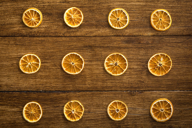Pattern of orange slices on a wooden table Fruit Table Wooden Festive Season  Christmas Decoration Grain Wood Backgrounds High Angle View Halloween Holiday Celebration Food Recipe Wellbeing Dried Orange Seasonal Rustic Decorative Scented Pattern Textured