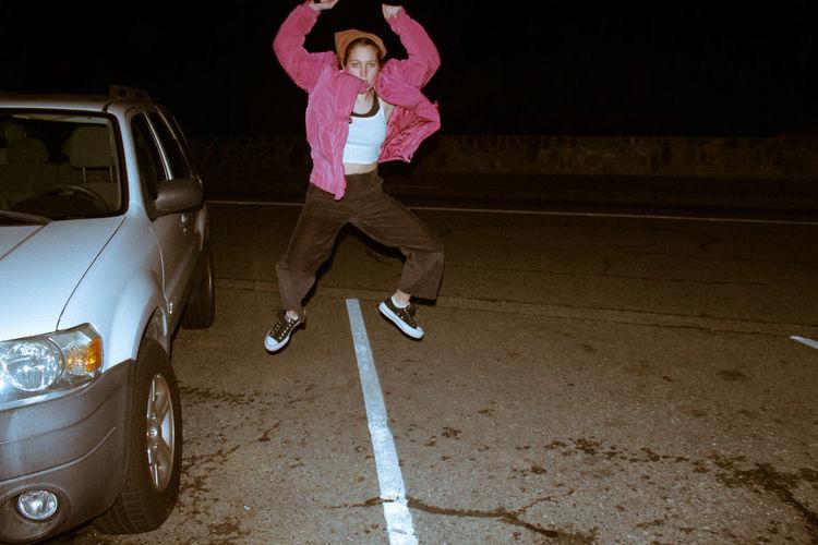 Full length of girl standing on car at night