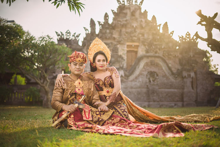 Portrait of smiling couple sitting against old ruins