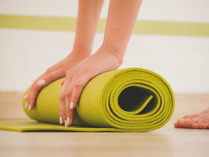 Process of preparing for class. Young woman rolls apart green yoga mat in fitness studio. Freedom, health lifestyle concept. Close up shot Yoga Couple Man Nature Practice Pray Woman Working Yoga Mat Acrobatic Activity Acrobatics  Asana Awesome Beauty In Nature Fitness Girl Pair Portrait Practicing Professional Religion Sea Sport Studio Shot Style