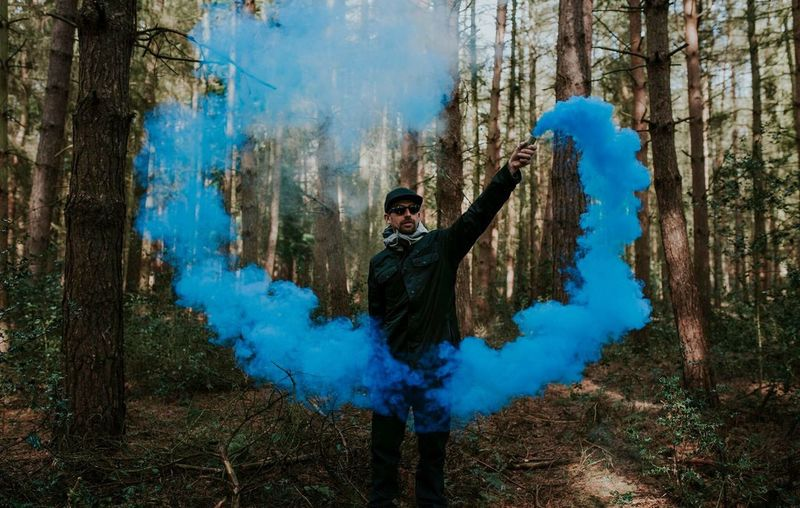 Young Man Holding Distress Flare While Standing In Forest