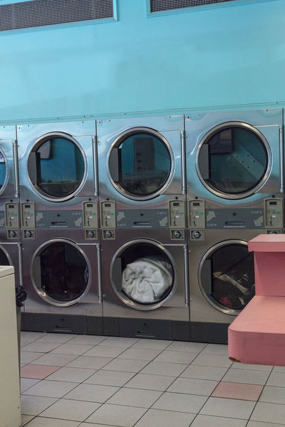 Washing clothes and drying at the Laundromat with chrome washer and dryer units along the isle and walls. Clean Day Dryer  Laundromat Laundry Machine No People Washing Machine