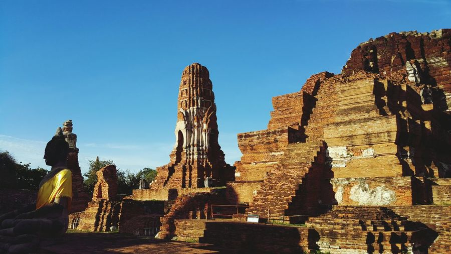 Panoramic view of buddha statue at temple against clear blue sky