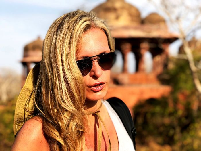 Close-Up Of Woman Wearing Sunglasses Against Historic Monument