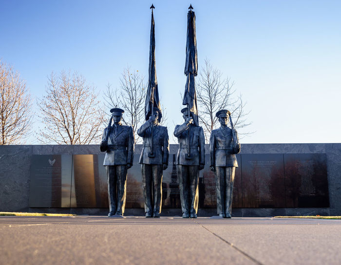 Air Force Memorial Art Art And Craft Casual Clothing Creativity Day Environmental Conservation Full Length Human Representation Lifestyles Men Occupation Outdoors Protection Real People Religion Safety Sitting Soldier Standing Statue
