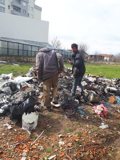Man working with garbage in front of built structure
