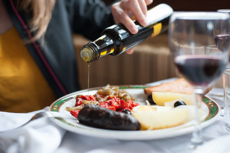 Detail of plate of escalivada with baked sausage. Alcohol Business Drink Food Food And Drink Freshness Glass Hand Holding Indoors  Midsection One Person Plate Preparation  Real People Red Wine Refreshment Selective Focus Serving Size Table Wine Wineglass