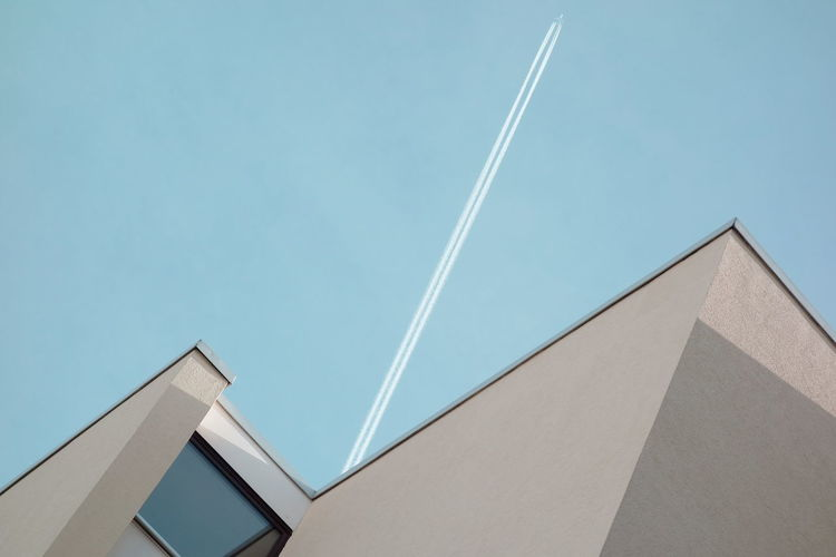 Low Angle View Of Vapor Trail Over Building Against Clear Blue Sky