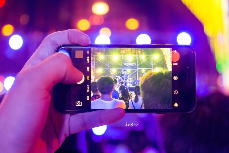 Midsection of woman using smart phone at music concert