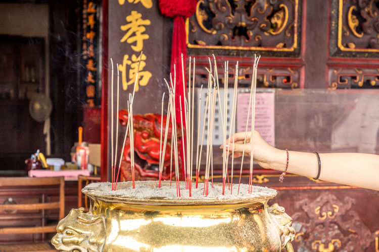 Hand lights a candle in front of a buddhist temple