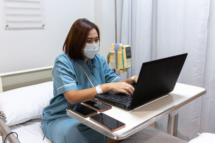 Illness asian patient women still  using laptop for working hard  in patient room of hospital