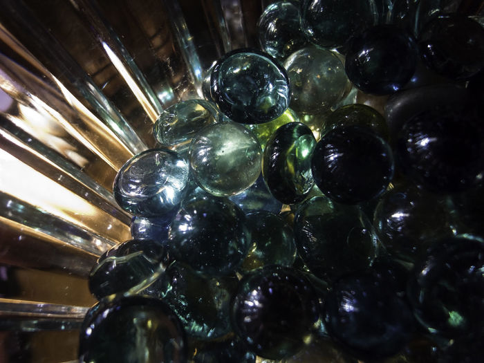 A crystal bowl containing marbles and stones, sunlight is shining and reflecting off these marbles and shiny stones. However, it was a section of the room where the overall light was less. Close-up Crystal Bowl Glass Bowl Glass Bowl With Marbles Light In A Crystal Bowl Light In A Glass Bowl Marbles Shining