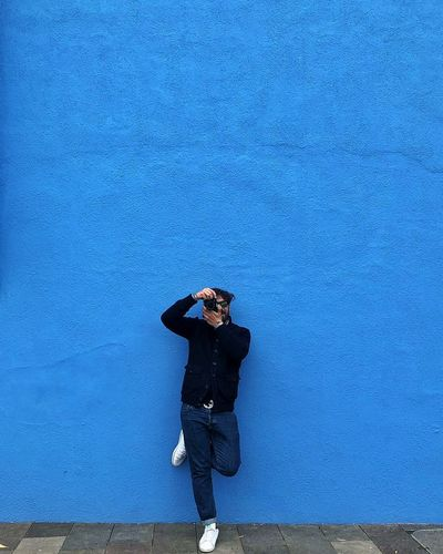 Young man looking away against blue wall