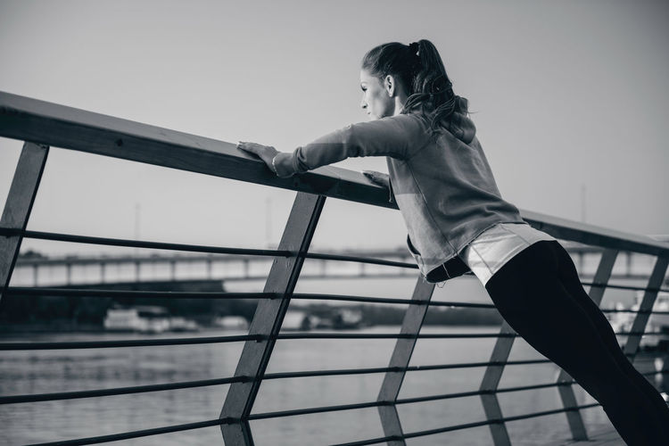 Woman exercising on railing against sky