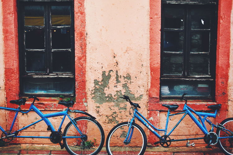 Close-up of bicycle against red house