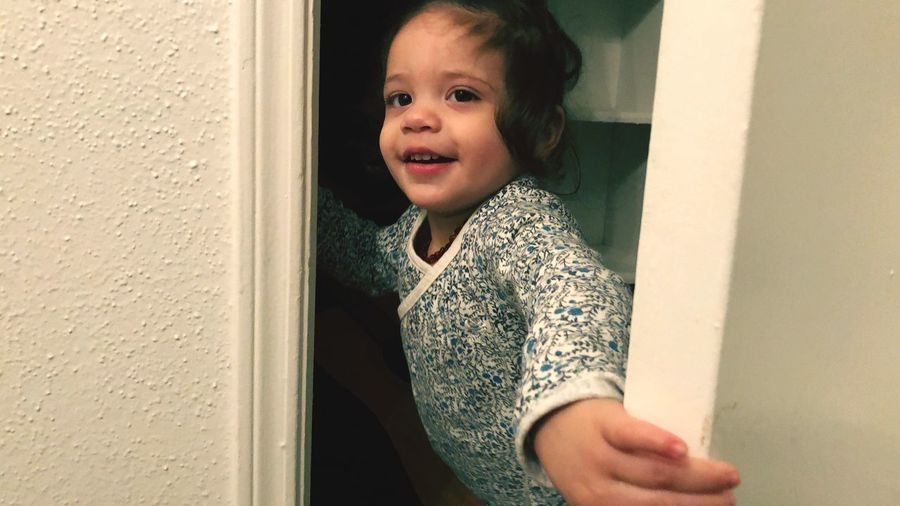 Cute baby girl closing door at home