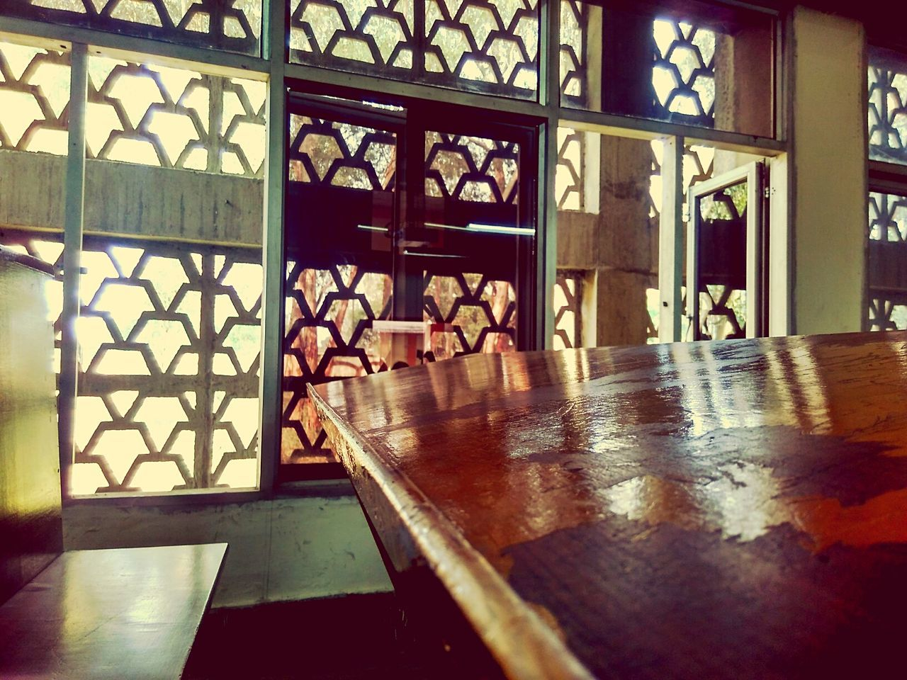 indoors, flooring, architecture, day, no people, table, window, built structure, wood - material, building, reflection, pattern, glass, seat, sunlight, spirituality, religion, wood, place of worship, architectural column, tiled floor, floral pattern