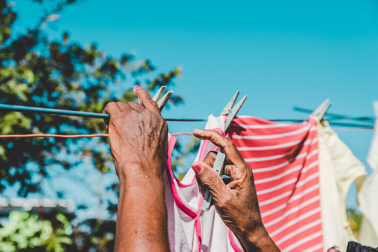 Cropped hands of woman hanging laundry on clothesline against clear blue sky