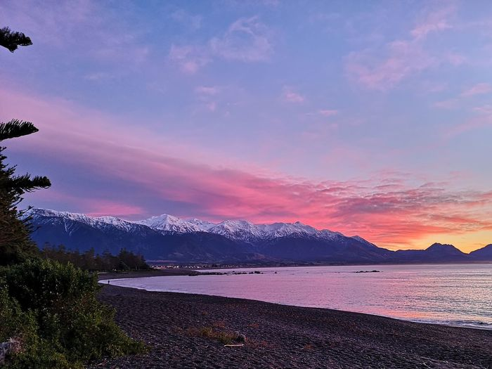 EyeEm Selects Mountain Snow Sunset Illuminated Pink Color Lake Tree Sky Landscape Mountain Range Snow Covered Snowcapped Mountain Romantic Sky Cold Temperature Winter Coast Mountain Peak Shore Snowcapped The Great Outdoors - 2018 EyeEm Awards