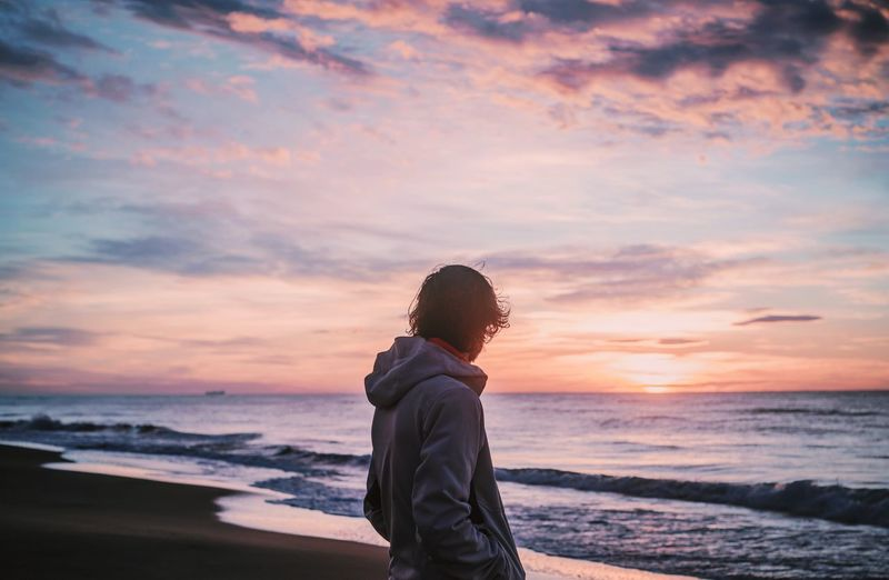 Man looking at sea against sunset sky
