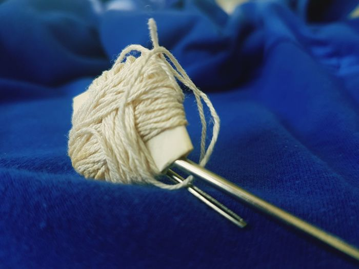 Close-Up Of Knitting Needles And Wool On Blue Textile