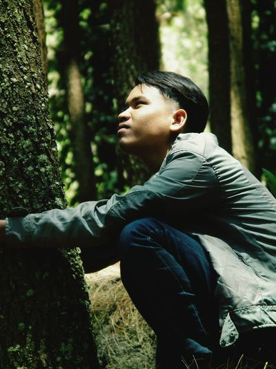 Side view of young man looking away while crouching in forest