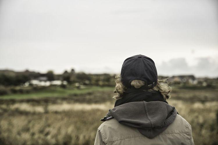 Rear view of woman looking away on field