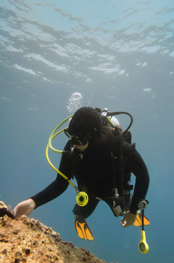 Scuba Diver Exploring Marine Life Underwater Scuba Diving Adventure Exploration Sea Wetsuit Marine Life Mediterranean  Activity Flippers Water Aquatic Sport UnderSea Nature Sea Life Extreme Sports underwater photography Woman Coral Reef Black Color One Person Diving Equipment Underwater Diving Scuba Mask Discovery
