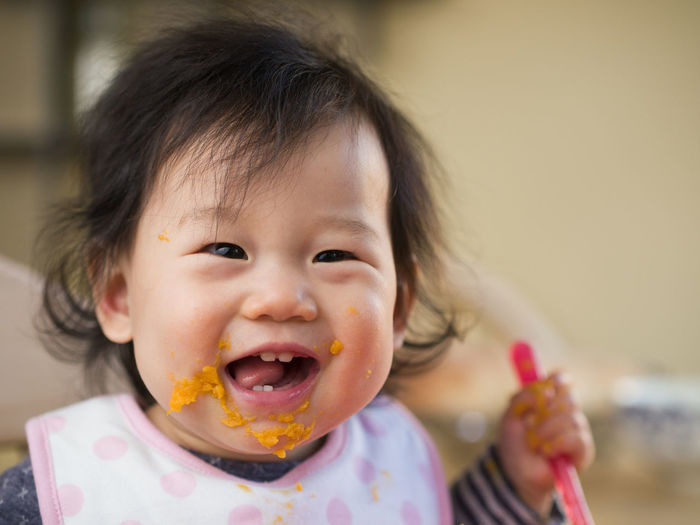 Close-up portrait of cute baby girl eating mashed potatoes at home
