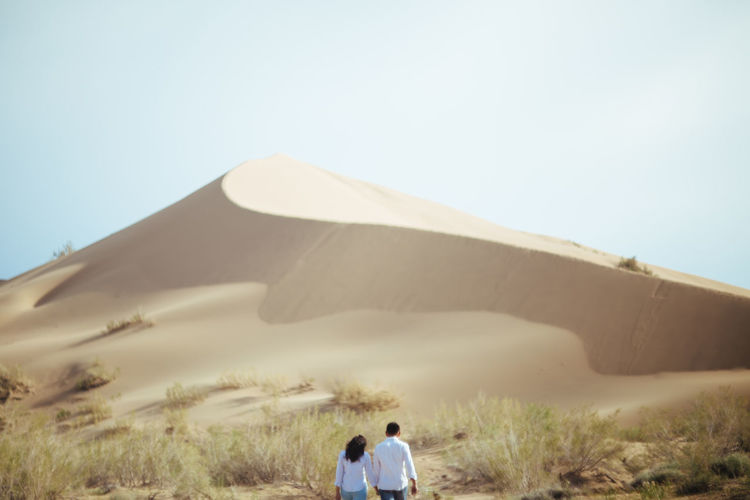 Rear view of the couple on sand dune against clear sky