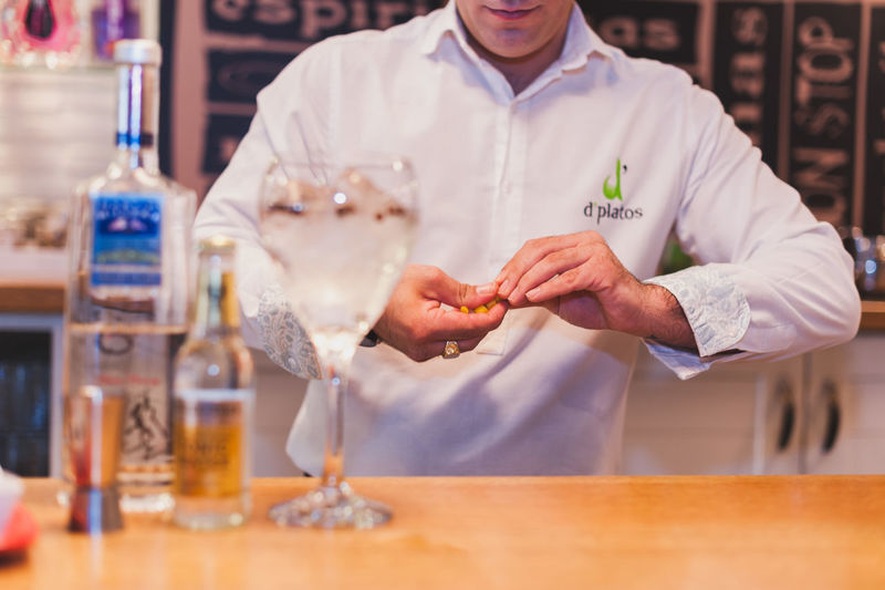 Midsection of bartender preparing drink at counter