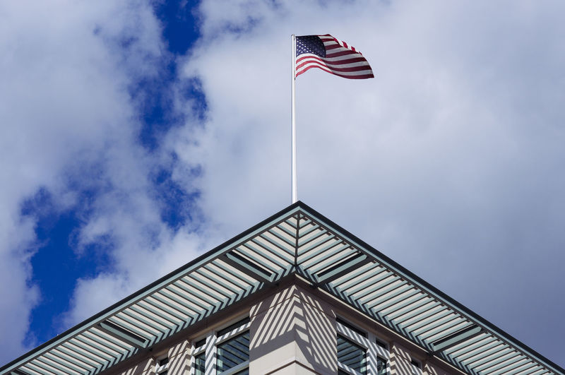 The american flag on the facade of a building against clouded sky