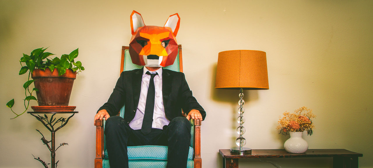 Businessman sitting on chair with fox mask in house
