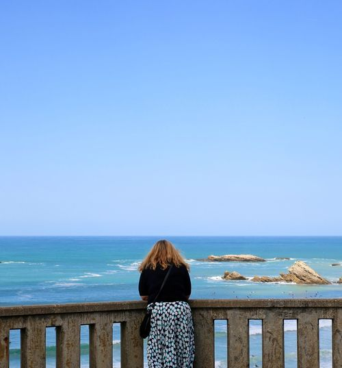 Rear view of woman leaning on railing against sea and clear sky