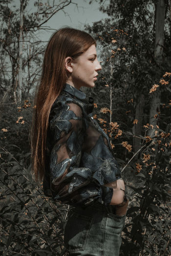 Side view of young woman in forest